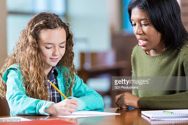 College age tutor helping elmentary age little girl with homework
