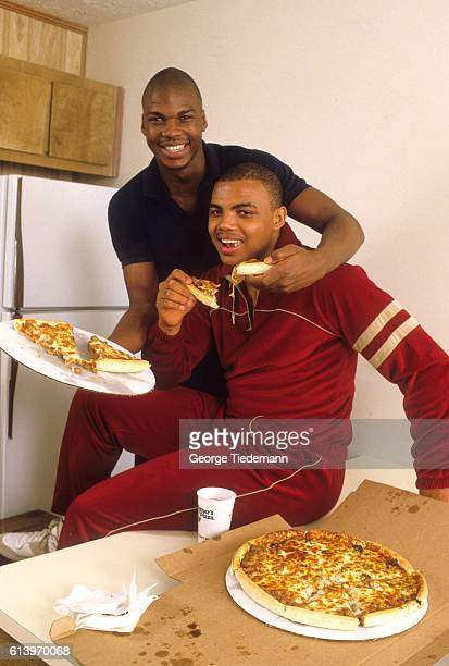 Casual portrait of Auburn Charles Barkley and teammate Chuck Person eating pizza during photo shoot Auburn AL CREDIT George Tiedemann