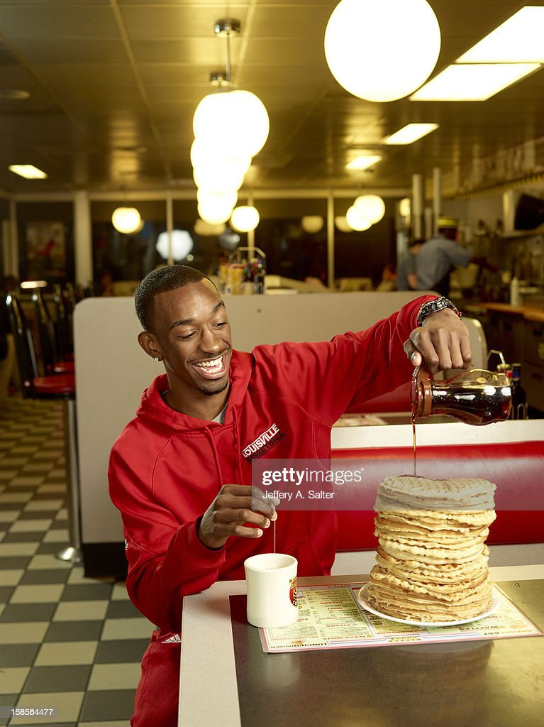 Casual portrait of Louisville Russ Smith posing while drinking tea and eating waffles during photo shoot at Waffle House on 4706 Preston Highway. Jeffery A. Salter F58 )