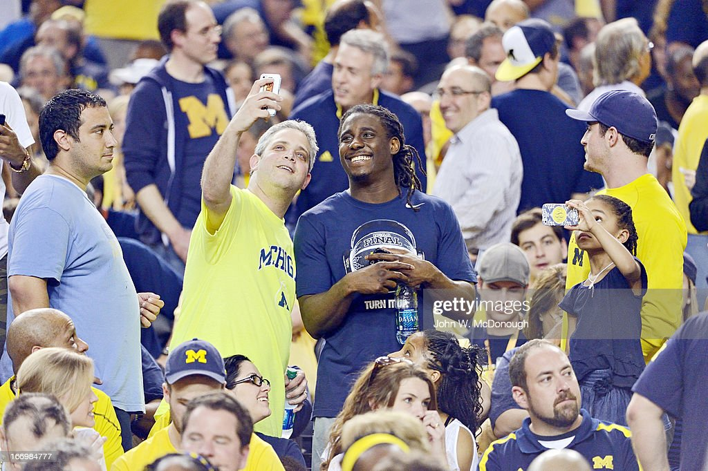 Former Michigan football QB Denard Robinson in stands with Michigan fan during game vs Louisville at Georgia Dome. John W. McDonough X156382 TK1 R5 F11 )