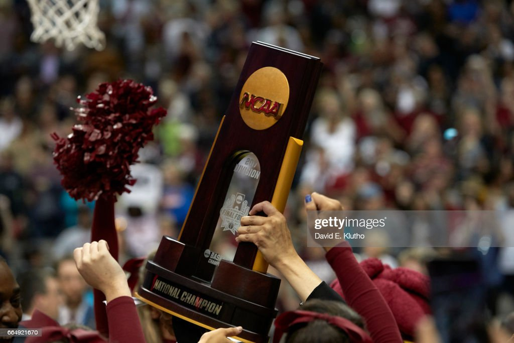 Closeup of NCAA Championship being held up by South Carolina players after winning game vs Mississippi State at American Airlines Center. David E. Klutho SI798 TK1 )
