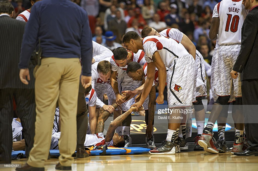Louisville Kevin Ware (5) on floor with teammates Peyton Siva (3) and Russ Smith (2) after suffering compound fracture leg injury during game vs Duke at Lucas Oil Stadium. Cover. David E. Klutho F89 )
