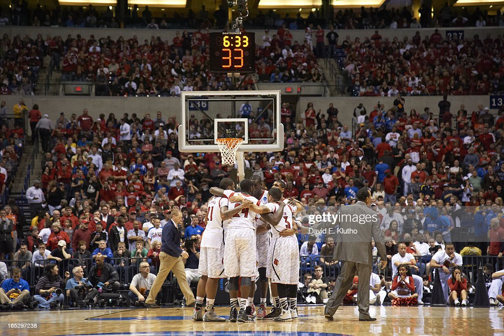 Louisville players in huddle on court after compound fracture leg injury to Kevin Ware (5) during game vs Duke at Lucas Oil Stadium. David E. Klutho X156331 TK1 R1 F8 )