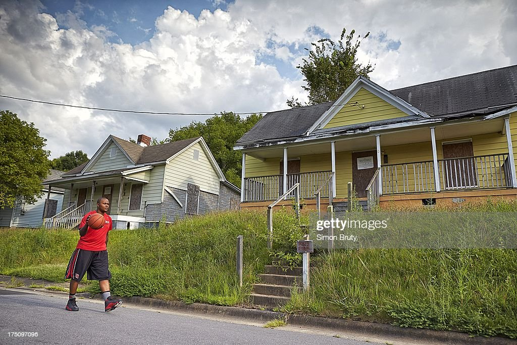Portrait of former UNC-Wilmington player Tyree Graham walking by his childhood home on Piedmont Avenue. Graham, who has played at multiple colleges and high schools during his career, represents the high frequency of transfers over the last seven seasons. Simon Bruty F229 )