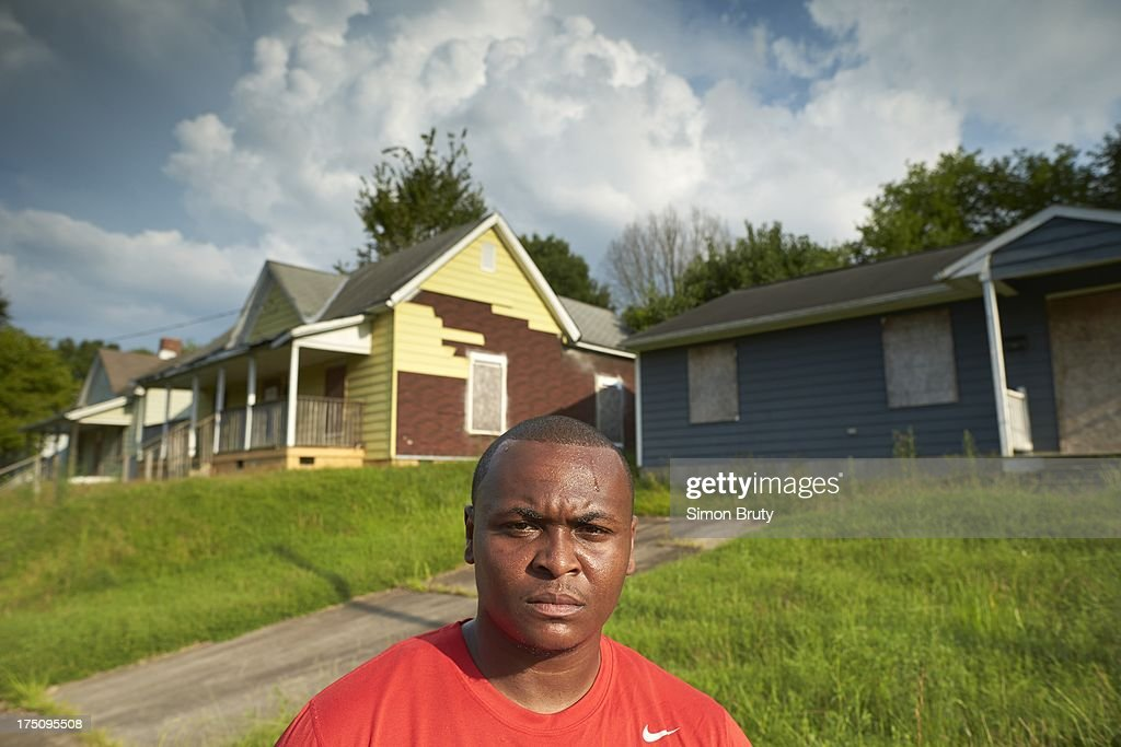 Portrait of former UNC-Wilmington player Tyree Graham in front of his childhood home on Piedmont Avenue. Graham, who has played at multiple colleges and high schools during his career, represents the high frequency of transfers over the last seven seasons. Simon Bruty F494 )