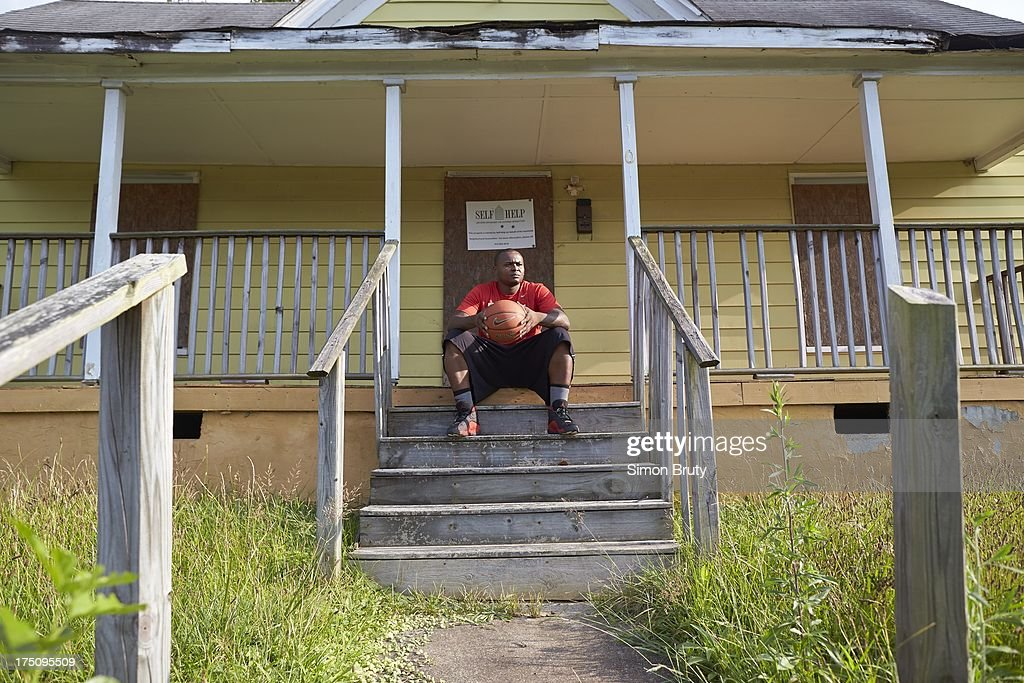 Portrait of former UNC-Wilmington player Tyree Graham in front of his childhood home on Piedmont Avenue. Graham, who has played at multiple colleges and high schools during his career, represents the high frequency of transfers over the last seven seasons. Simon Bruty F361 )