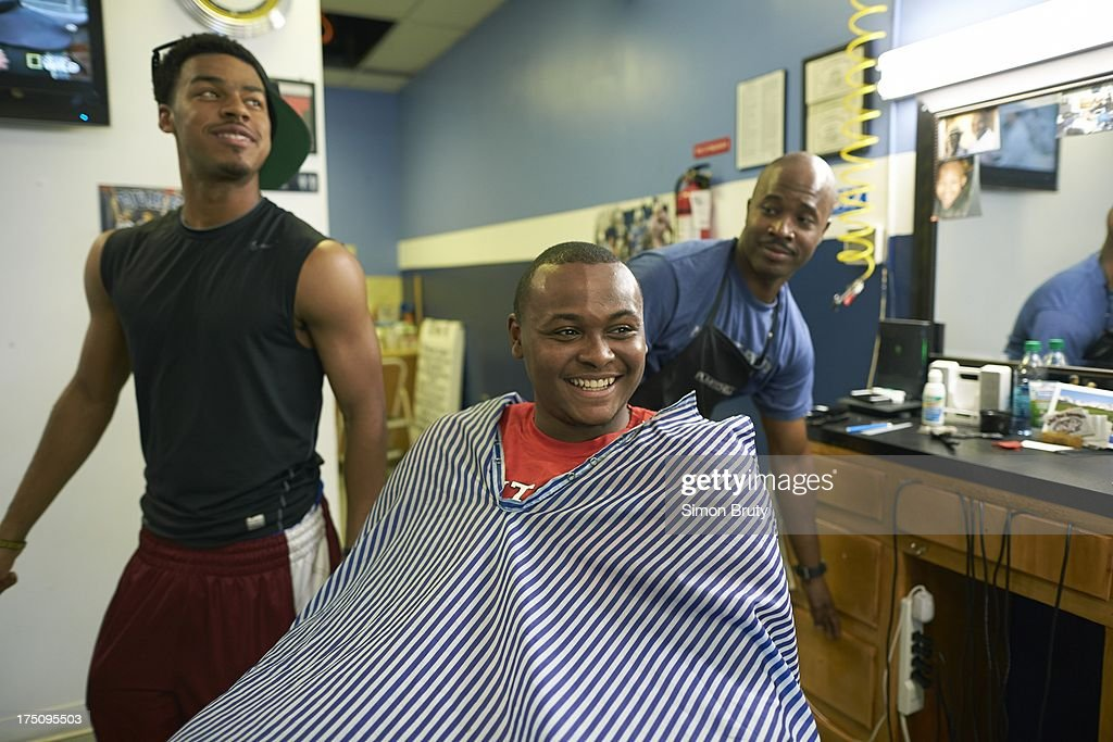 Portrait of former UNC-Wilmington player Tyree Graham getting his hair cut by Len Lilly at Forty Below Barber Shop. Graham, who has played at multiple colleges and high schools during his career, represents the high frequency of transfers over the last seven seasons. Simon Bruty F31 )