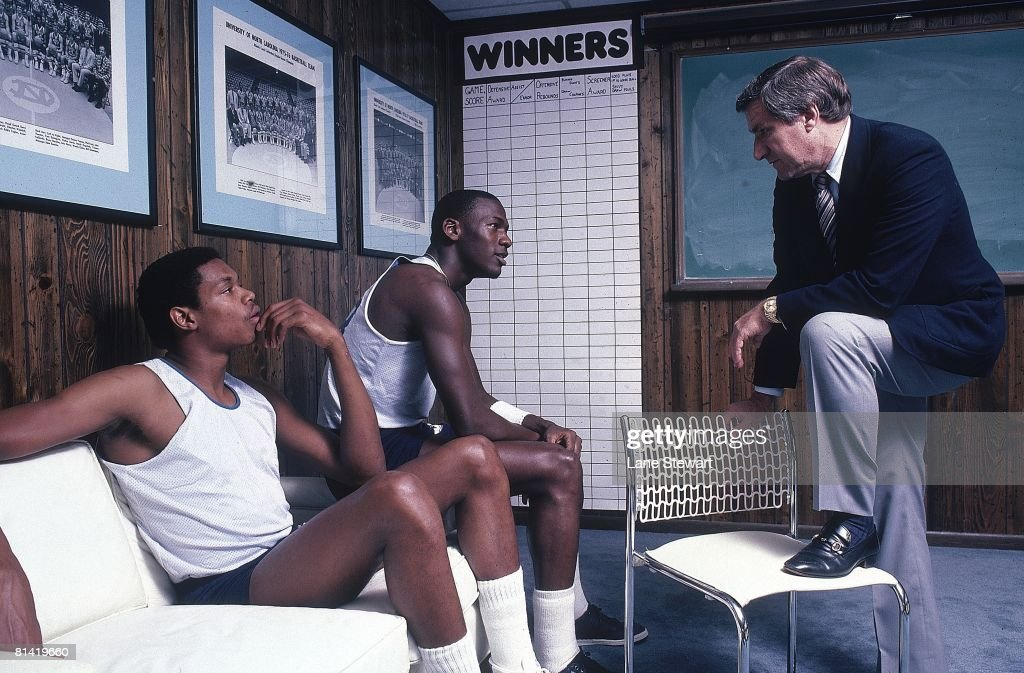 Portrait of North Carolina Sam Perkins (41), Michael Jordan (23), and coach Dean Smith in office at University of North Carolina, Chapel Hill, NC