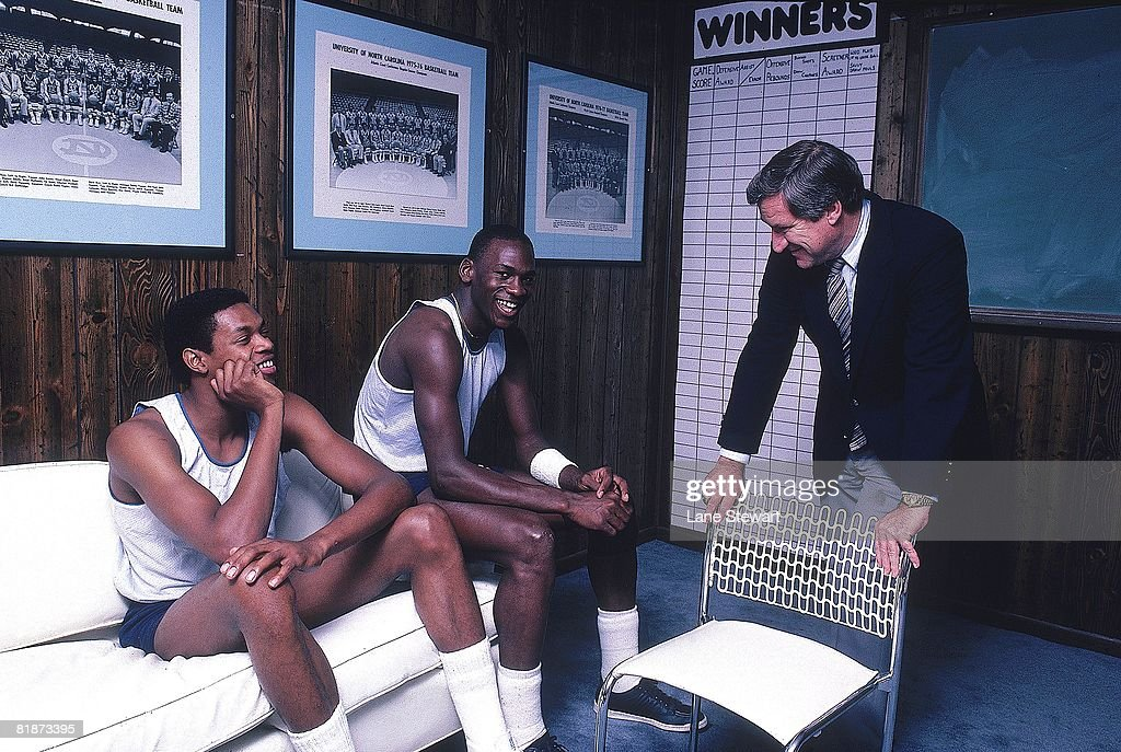 Portrait of North Carolina Sam Perkins (41), Michael Jordan (23), and coach Dean Smith in office at University of North Carolina. Chapel Hill, NC