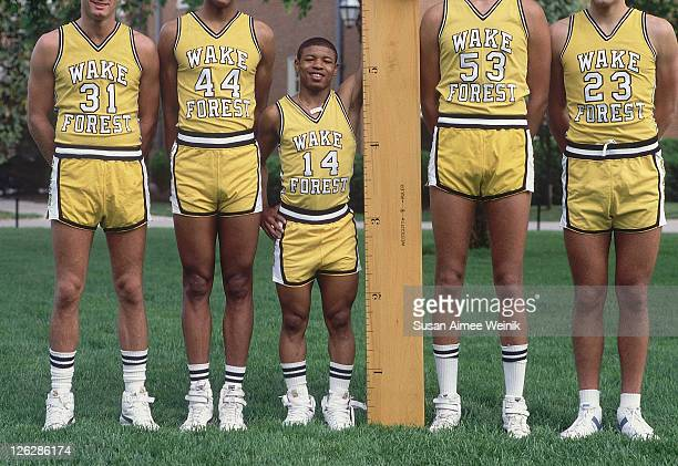 Portrait of Wake Forest Tyrone 'Muggsy' Bogues standing next to an oversized ruler with teammates during photo shoot on Wake Forest University campus...