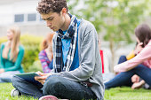 Serious young college boy using tablet PC with blurred students sitting in the park
