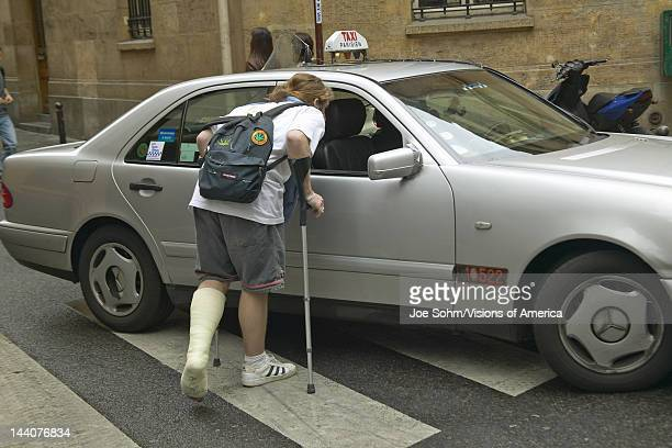 College boy with broken leg flagging down taxi Paris France