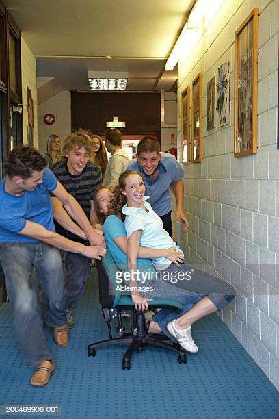 College boys pushing girls along on chairs, smiling, portrait