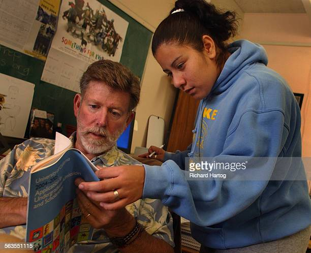 College counselor John Mandell left works with senior Maribel Magana as she and fellow students prepare to send off their UC applications at Locke...