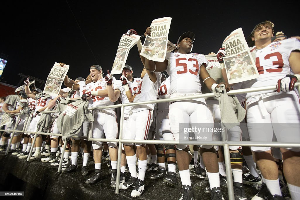 Alabama Michael Nysewander (46), Anthony Orr (53) and Cade Foster (43) victorious holding up newspapers after winning game vs Notre Dame at Sun Life Stadium. Simon Bruty F169 )