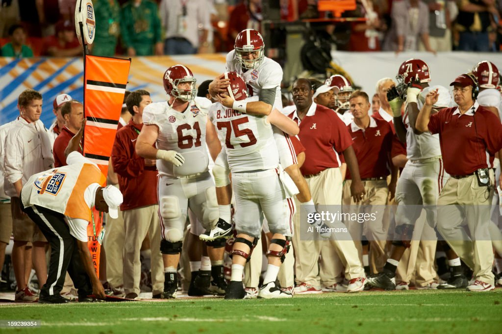 Alabama QB A.J. McCarron (10) and Barrett Jones (75) victorious on sidelines during game vs Notre Dame at Sun Life Stadium. Al Tielemans F109 )