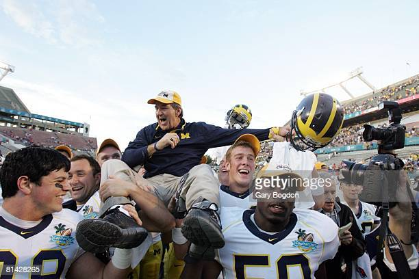 College Football Capital One Bowl Michigan Coach Lloyd Carr victorious getting carried off field by team after winning game vs Florida Carr's final...