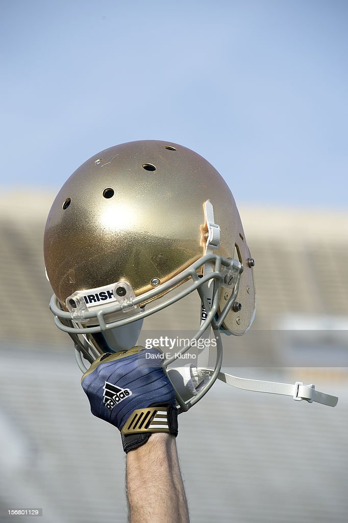 Closeup portrait of hand holding Notre Dame helmet during photo shoot at Notre Dame Stadium. Cover. David E. Klutho F38 )