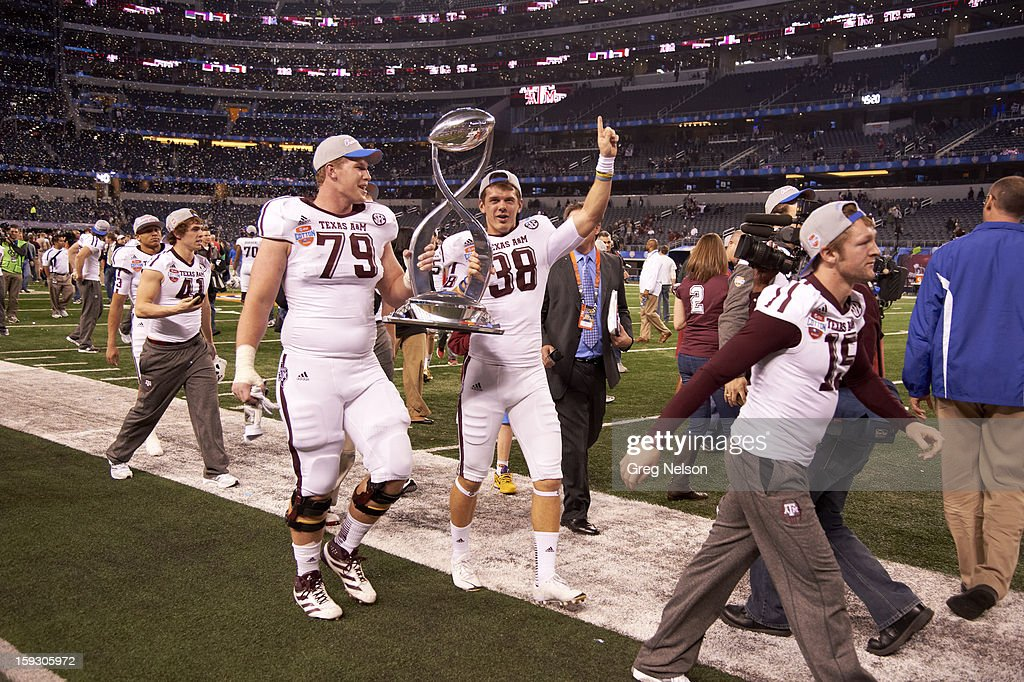 Texas A&M Drew Kaser (38) and Joseph Cheek (79) victorious holding Cotton Bowl trophy after winning game vs Oklahoma at Cowboys Stadium. Greg Nelson F171 )