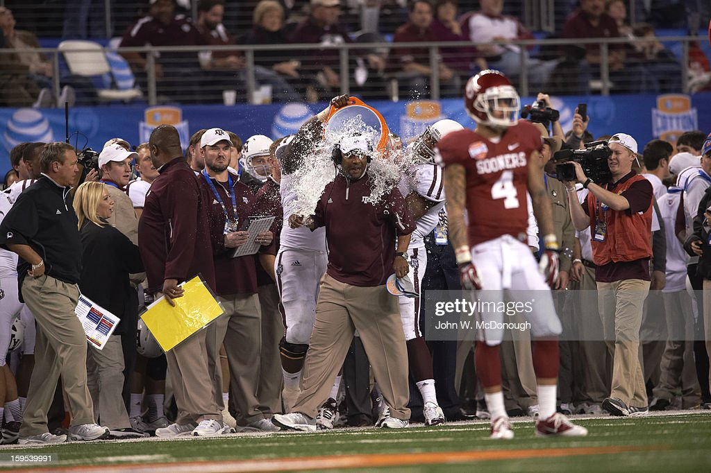 Texas A&M head coach Kevin Sumlin victorious as his players empty gatorade cooler on him after winning game vs Oklahoma at Cowboys Stadium. Sequence. John W. McDonough F485 )