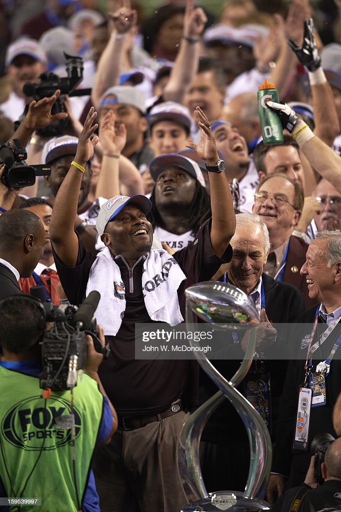 Texas A&M head coach Kevin Sumlin victorious after winning game vs Oklahoma at Cowboys Stadium. View of Cotton Bowl Trophy. John W. McDonough F517 )