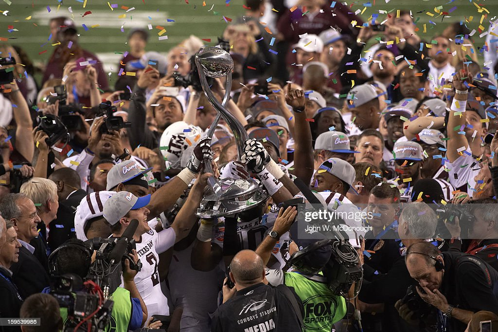 Texas A&M QB Johnny Manziel (2) and teammates victorious on field with trophy after winning game vs Oklahoma at Cowboys Stadium. John W. McDonough F484 )