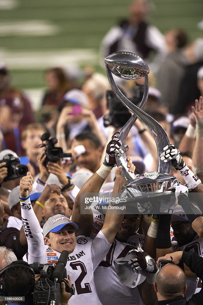 Texas A&M QB Johnny Manziel (2) and teammates victorious on field with trophy after winning game vs Oklahoma at Cowboys Stadium. John W. McDonough F532 )