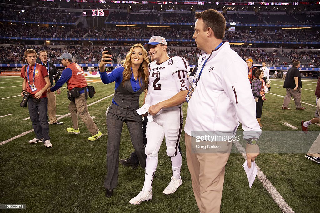 Texas A&M QB Johnny Manziel (2) victorious on field taking picture with female fan after winning game vs Oklahoma at Cowboys Stadium. Greg Nelson F108 )