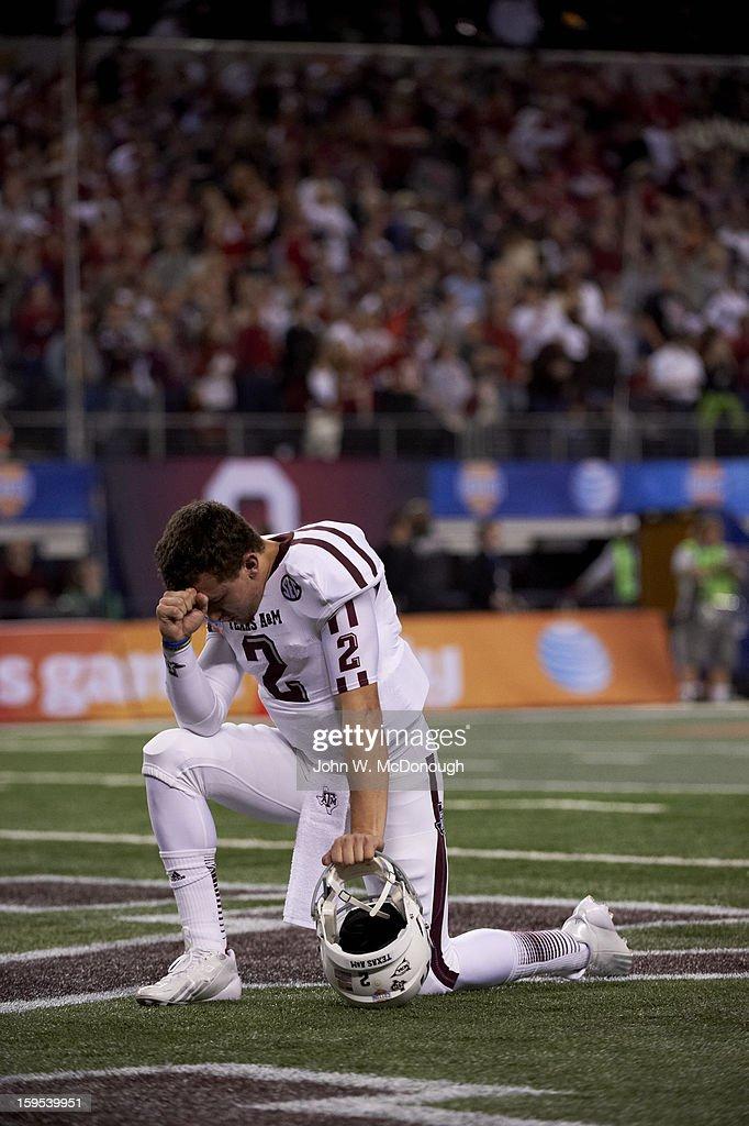 Texas A&M QB Johnny Manziel (2) kneeling on field in prayer before game vs Oklahoma at Cowboys Stadium. John W. McDonough F17 )