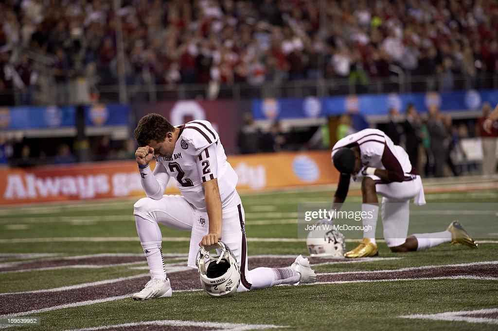 Texas A&M QB Johnny Manziel (2) kneeling on field in prayer before game vs Oklahoma at Cowboys Stadium. John W. McDonough F55 )