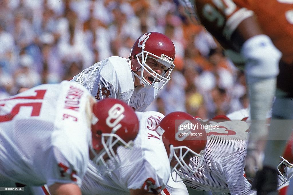 Oklahoma QB Troy Aikman (18) calling signals at line of scrimmage before snap vs Texas. Dallas, TX