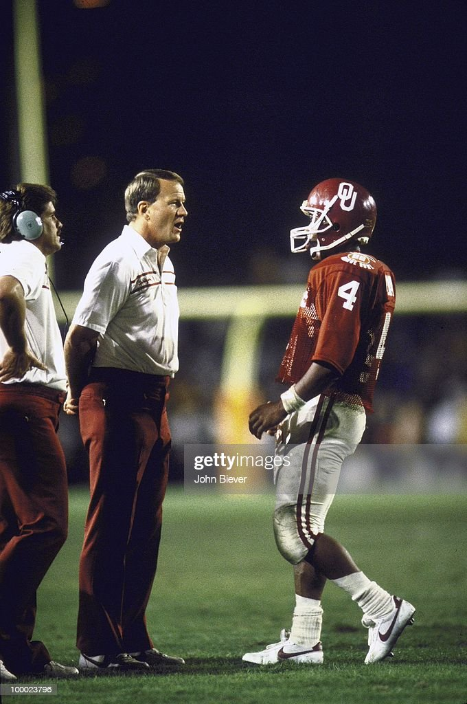 Oklahoma coach Barry Switzer talking with QB Jamelle Holieway (4) during game vs Penn State. Miami, FL 1/1/1986