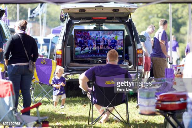 View of East Carolina fans tailgating before game vs South Florida outside of DowdyFicklen Stadium Fan watching pregame show on big screen in the...