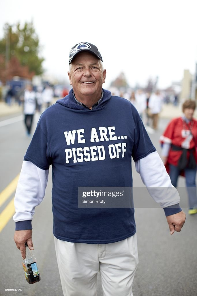 View of fan wearing shirt reading WE ARE... PISSED OFF! outside stadium before Penn State vs Ohio State game at Beaver Stadium. Simon Bruty F51 )
