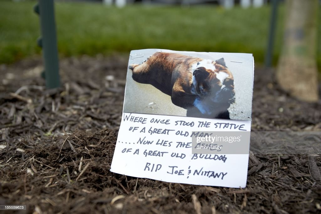 View of sign reading WHERE ONCE STOOD THE STATUE OF A GREAT OLD MAN... NOW LIES THE ASHES OF A GREAT OLD BULLDOG. R.I.P. JOE AND NITTANY left by fan during memorial of coach Joe Paterno before Penn State vs Ohio State game at Beaver Stadium. Simon Bruty F44 )