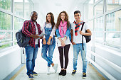 Friendly students in casual-wear standing in college corridor