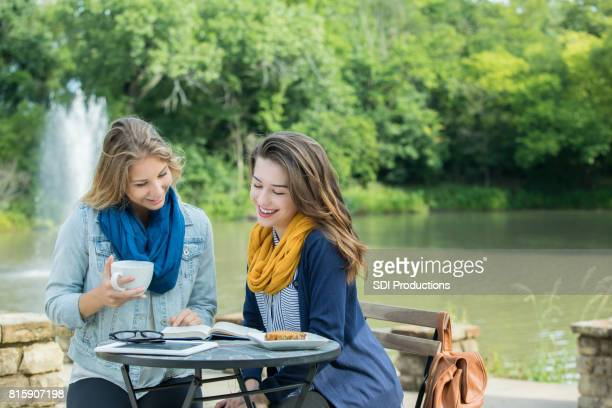 College friends study together at outdoor cafe