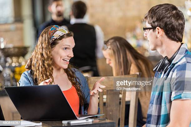 College friends using laptop during study date in coffee shop