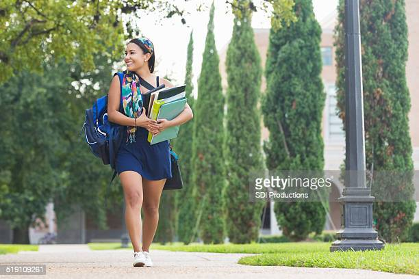 College girl carrying heavy books to class on campus