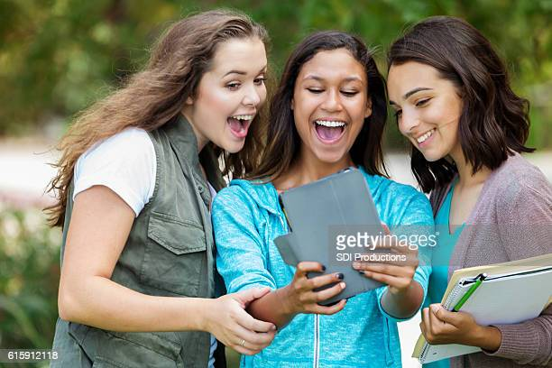 College girls using a digital tablet to take selfie photo