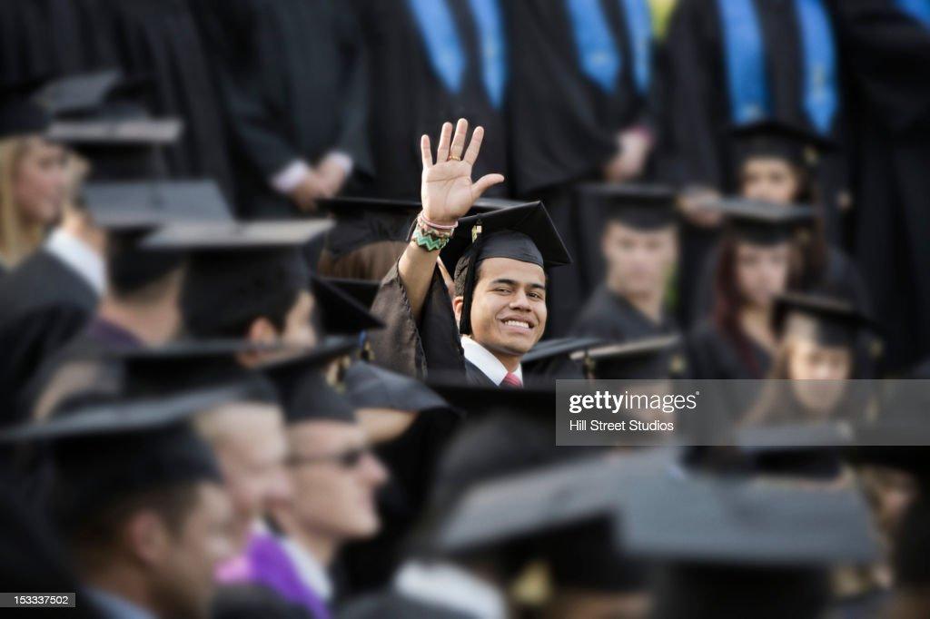 College graduate waving