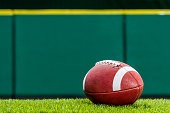 A low angle view, of a textured College or High School American Football made of leather with white stripe sitting on artificial turf of a stadium with green padded wall in the background. This type o
