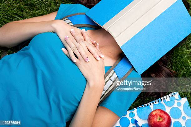 College student sleeping under her book