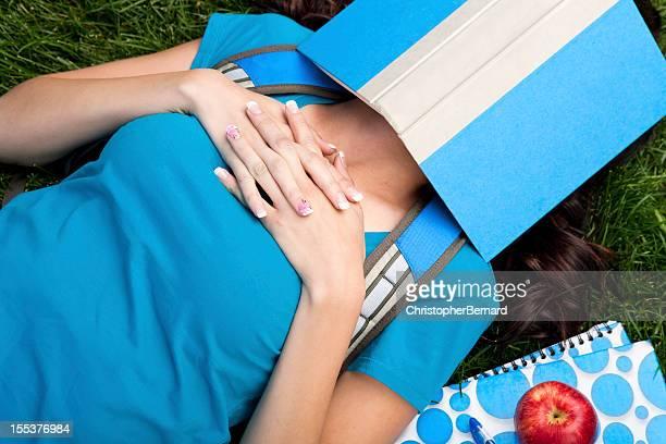 College student sleeping under her book