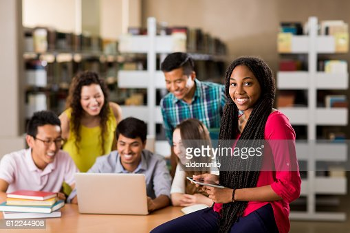 College student smiling at camera with people in background