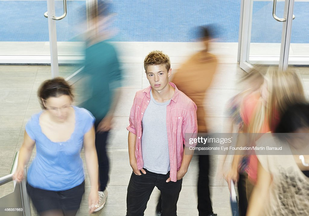 College student standing in busy hallway : Stock Photo