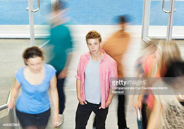 College student standing in busy hallway