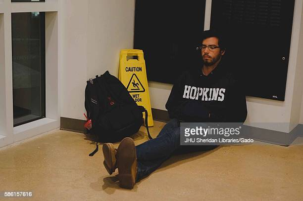 A college student taking a nap while sitting against a wall in Brody Learning Commons at Johns Hopkins University his backpack and a Caution Wet...