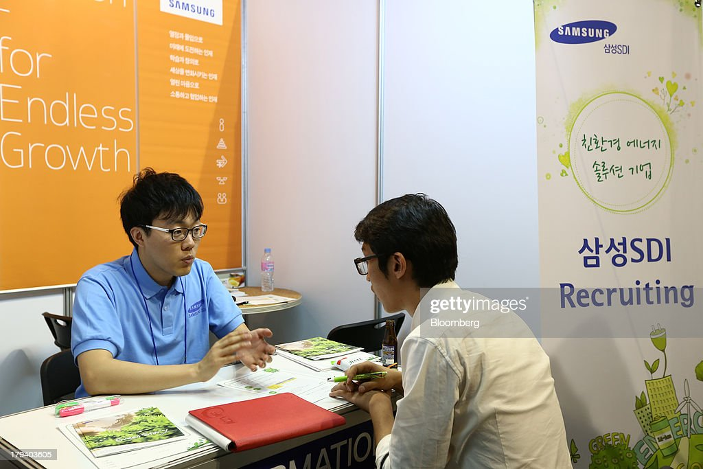 A college student talks to a Samsung SDI Co recruiter during a job fair at Hanyang University in Seoul South Korea on Tuesday Sept 3 2013 South Korea...