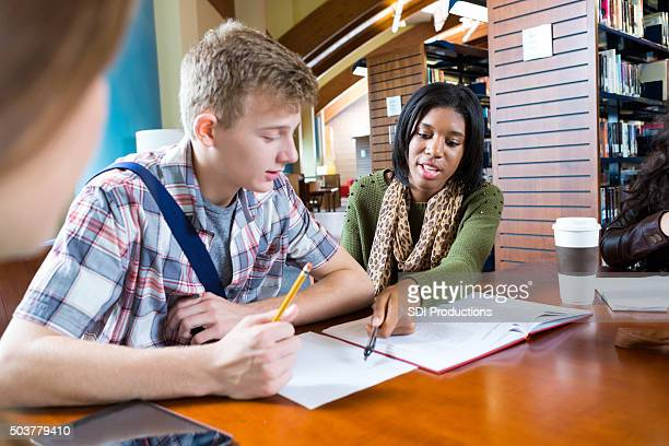 College student tutoring high school boy in modern library